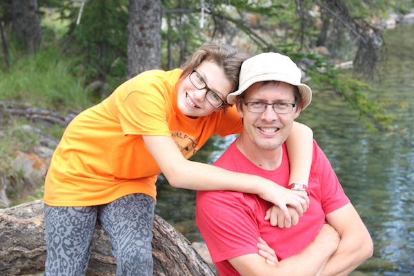 A young girl with glasses with her arms wrapped around a man with a fishing hat and glasses. They are sitting on a wooden log next to a lake.