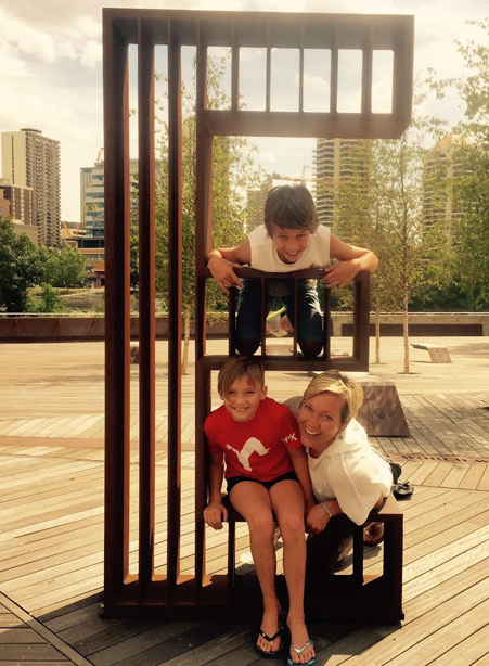 Katharina Doyle posing for a photo with her two young kids on a piece of public art that is shaped like the letter E.