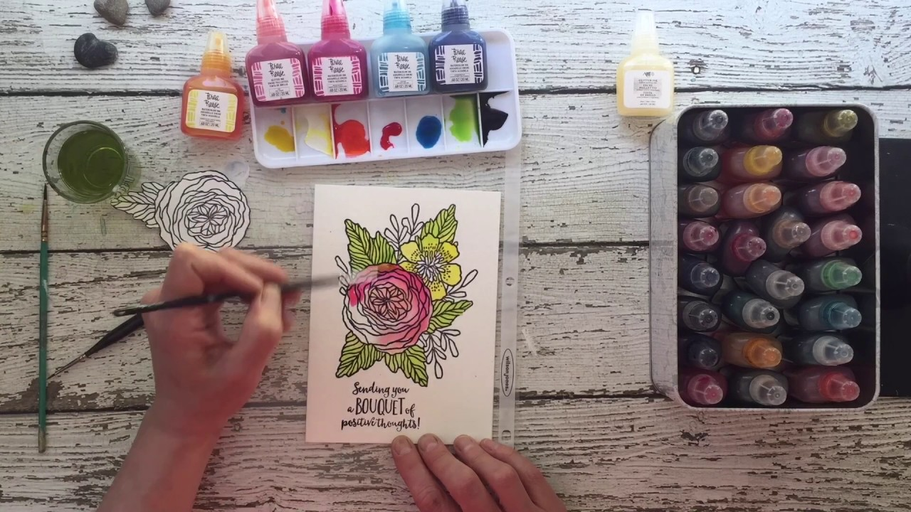 An artists painting a flower stamped image using Brea Reese watercolor ink.