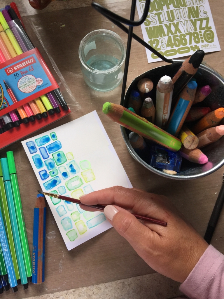 Using a wet paint brush to smear the colours on a card with rectangles that were drawn with Stabilo pens.