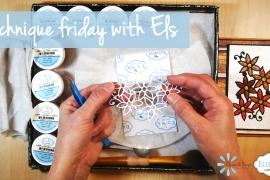Artist hands holding an Elizabeth Craft Designs die cut after running throw a die cut machine - about to add glitter