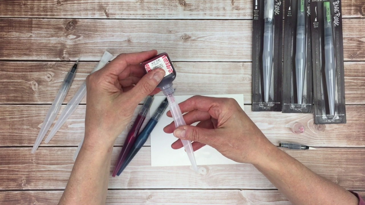An artist filling up a waterbrush paint brush with Brea Reese watercolor ink.