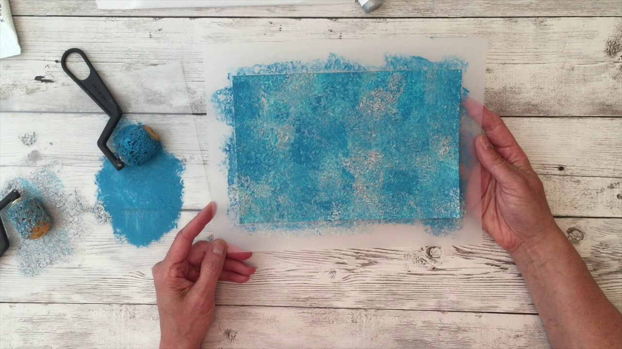 An artists painting texture on a piece of white paper using Brea Reese sponge like rollers and Brea Reese glitter paint.