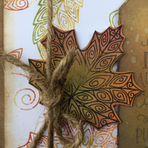 Closeup of leaf for fall card that as been stamped with Newton Nook stamps and the background created with Ranger oxide inks.