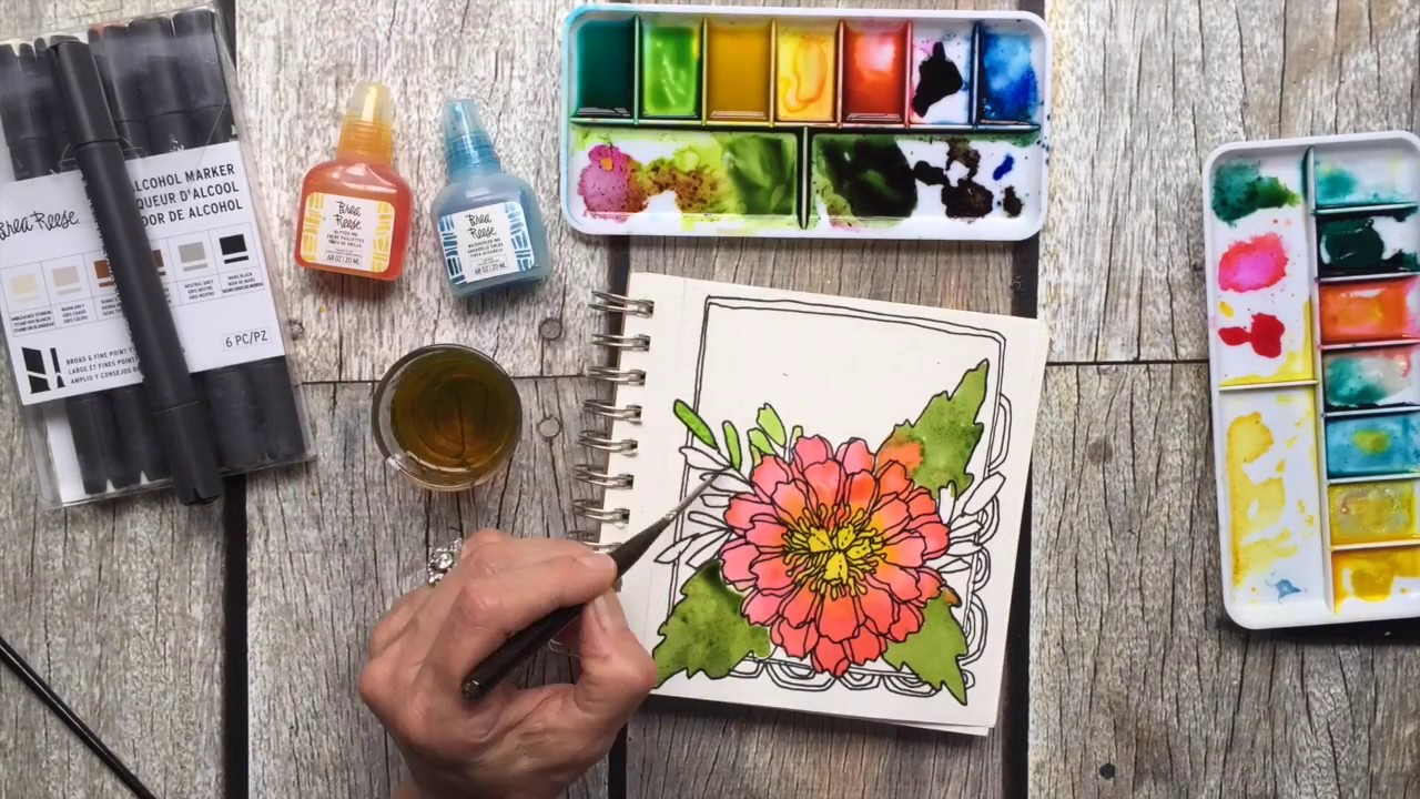 An artist painting in her art journal a flower image using Brea Reese markers and watercolor.