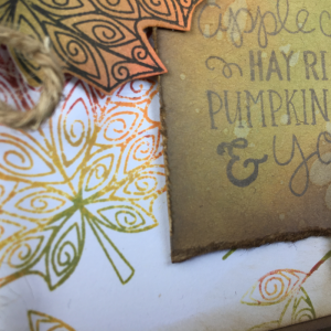 Closeup of tag for fall card that as been stamped with Newton Nook stamps and the background created with Ranger oxide inks.