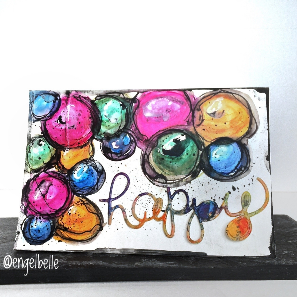 Scrapbook card with the word Happy on it surrounded by circles created with a variety of Stabilo products.