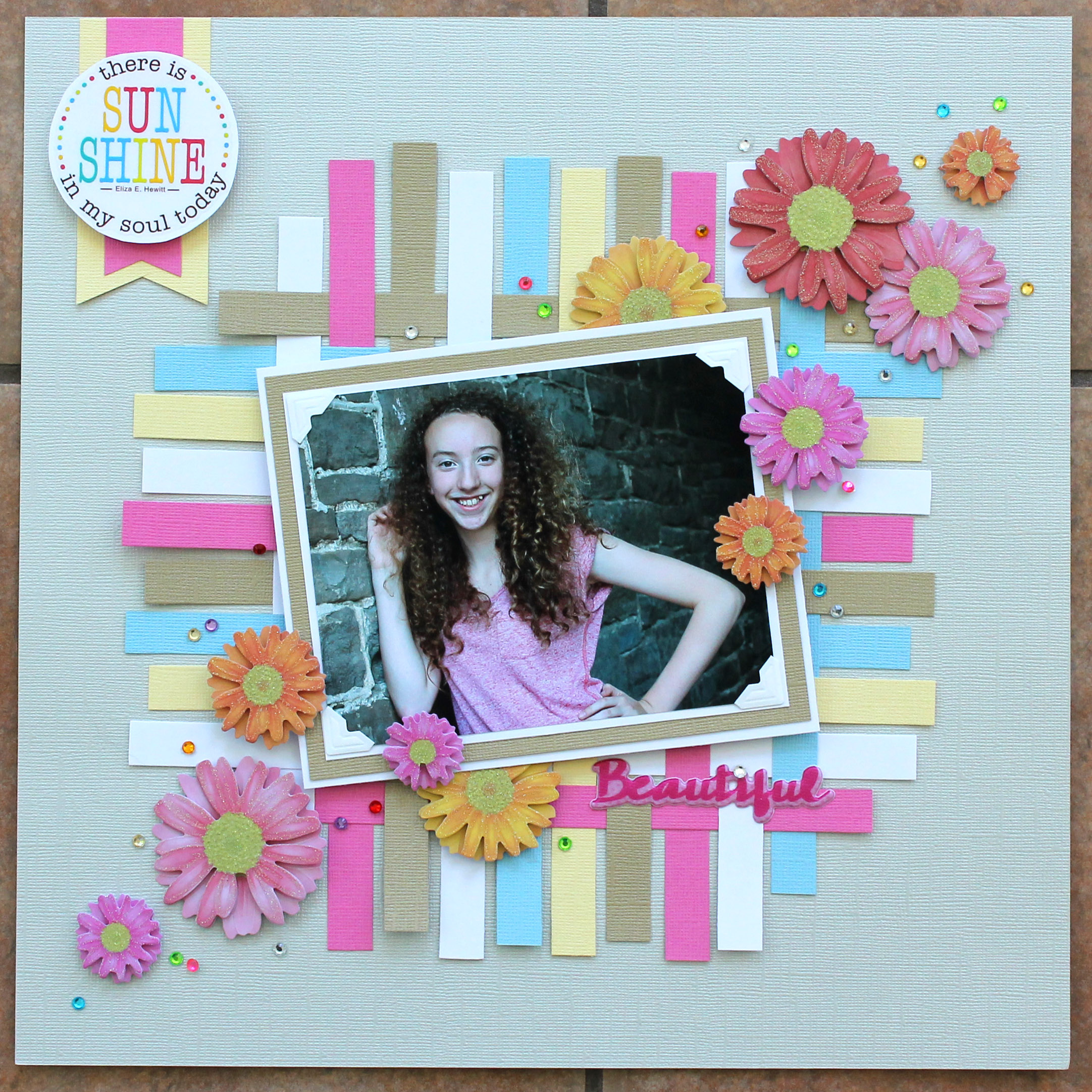 Scrapbooking projects designed by Tracy McLennon featuring MultiCraft of a teenage girl standing in front of a grey brick wall. The layout features paper weaving and flower stickers.