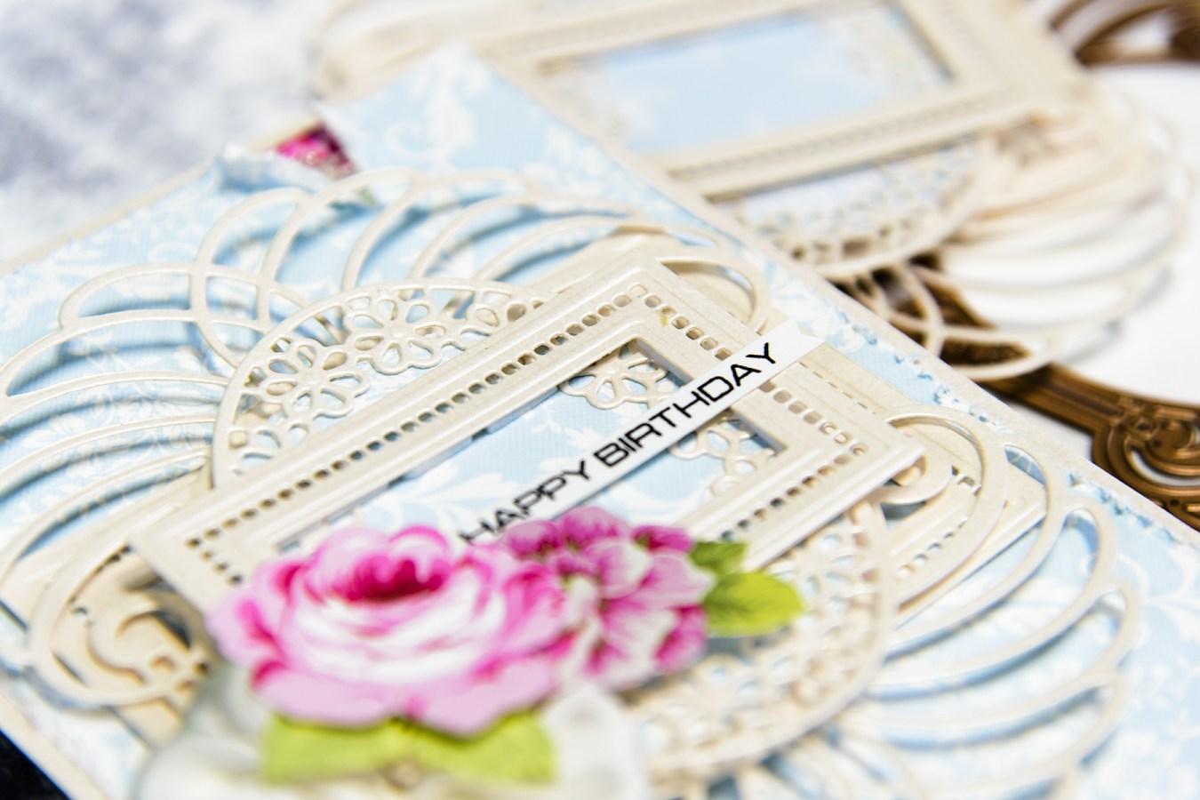 Close up of intricate layers of spellbinders dies on a scrapbooked birthday card