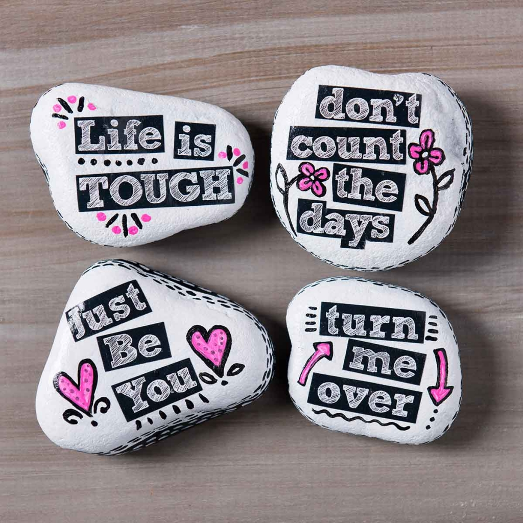 Four painted rocks with sentiments on them featuring Plaid products