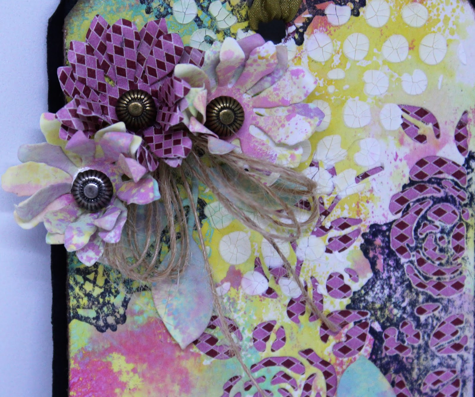 Detailed image of a Sizzix flower die on a mixed media tag