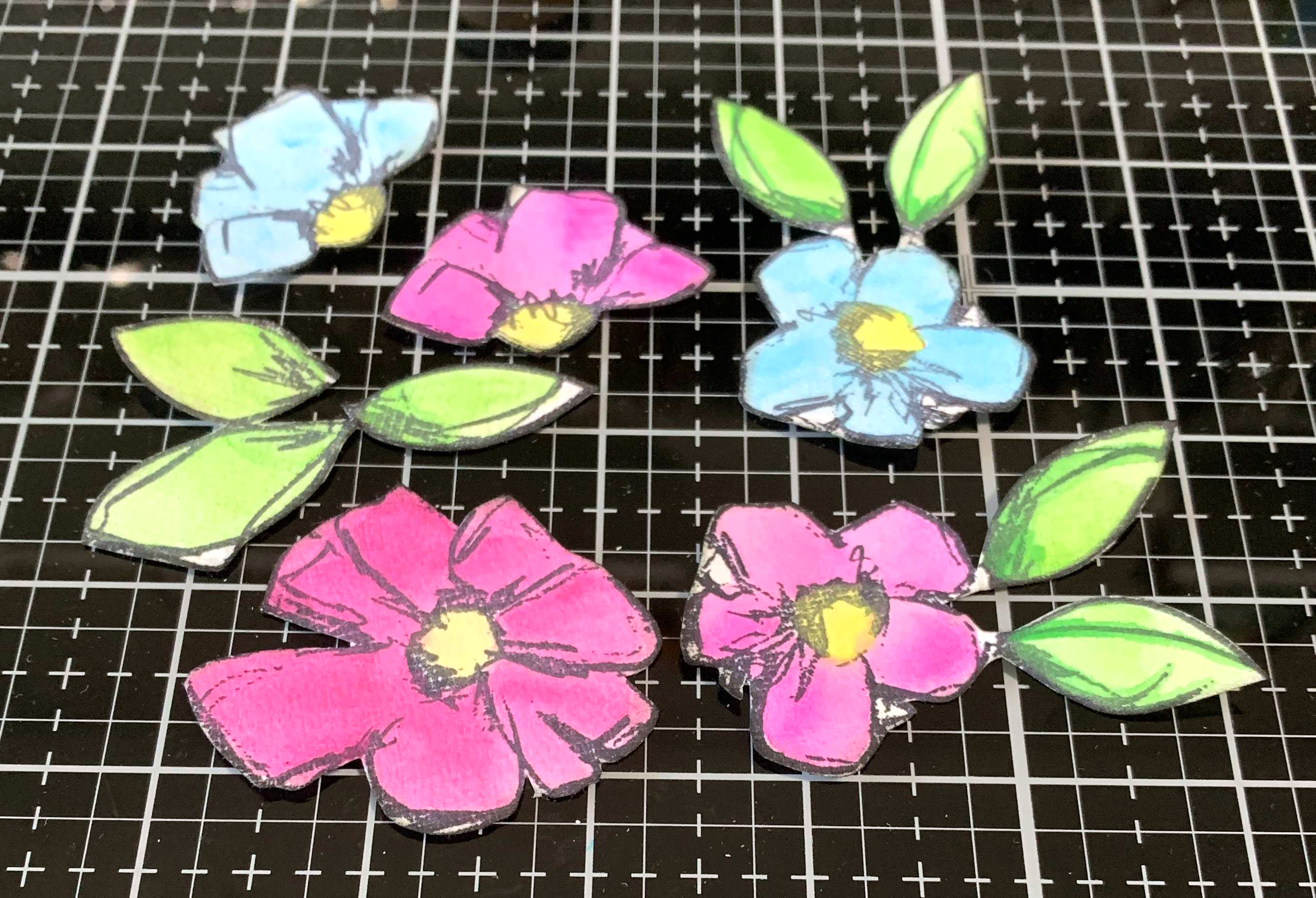 Flower embellishments created using Dina Wakley stamps and Scribble Sticks cut out of cardstock in bright colors.