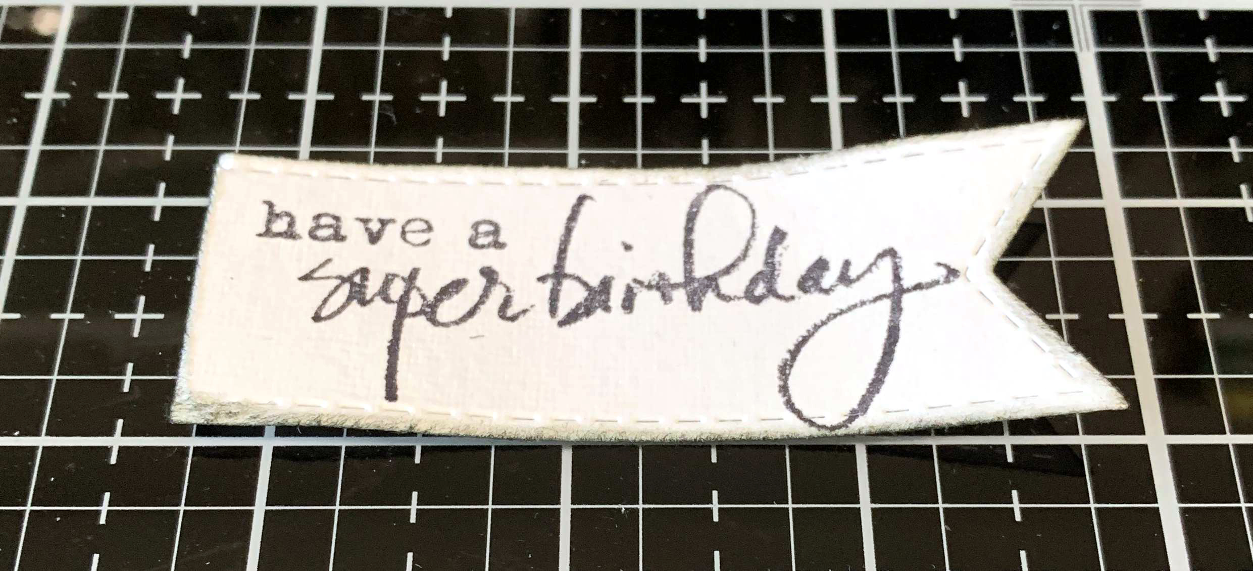 Birthday Sentiment stamped using a Dina Wakley stamp on a rectangular banner die by Elizabeth Craft Designs.