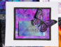 Butterfly scrapbook card in bright purples and blues featuring Ranger Tim Holtz Alcohol Ink Yupo paper and alcohol inks. Card designed by Jayme Loge
