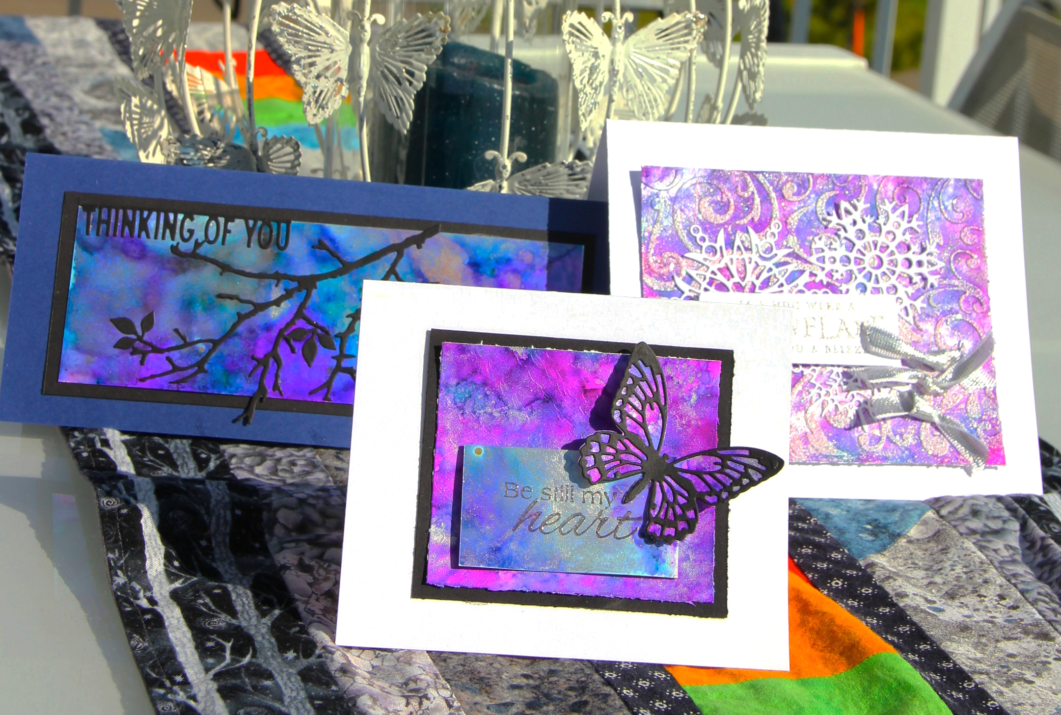 Scrapbook cards in bright purples and blues featuring Ranger Tim Holtz Alcohol Ink Yupo paper and alcohol inks. Card designed by Jayme Loge