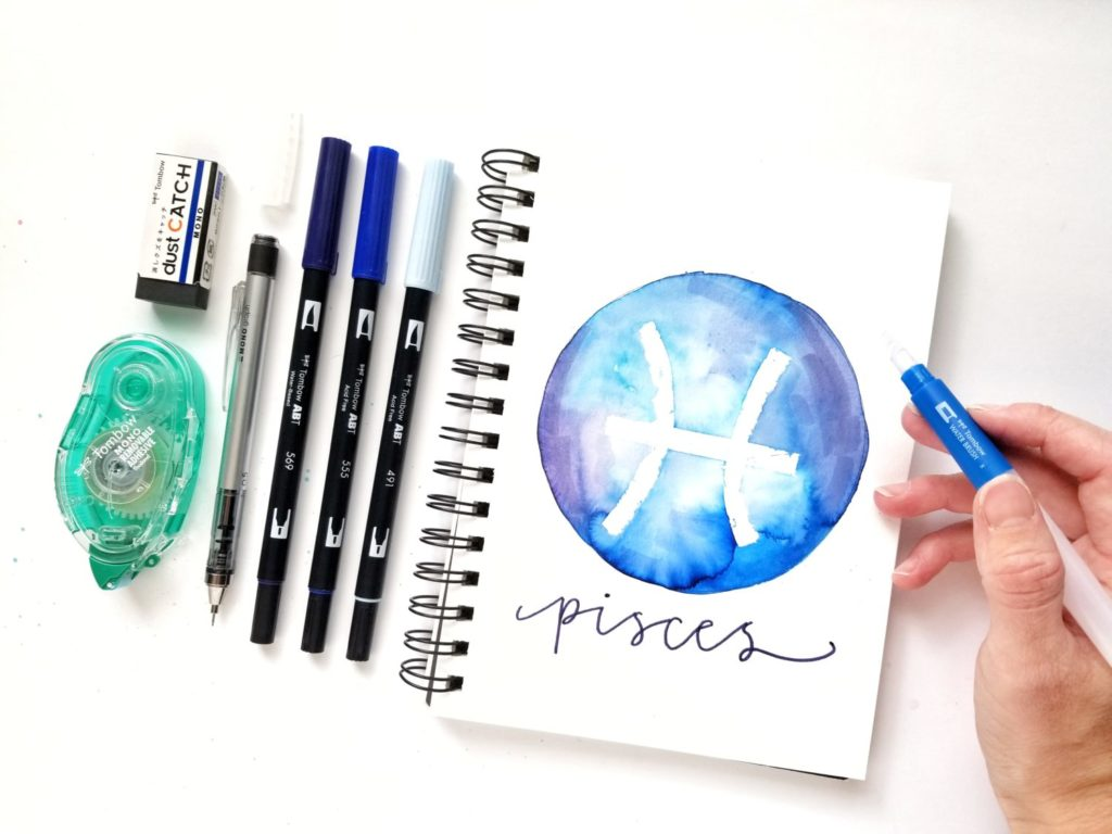 Watercolor art journal page in different shades of blue with a round circle and a zodiac sign designed by Grace Anne Studios featuring Tombow