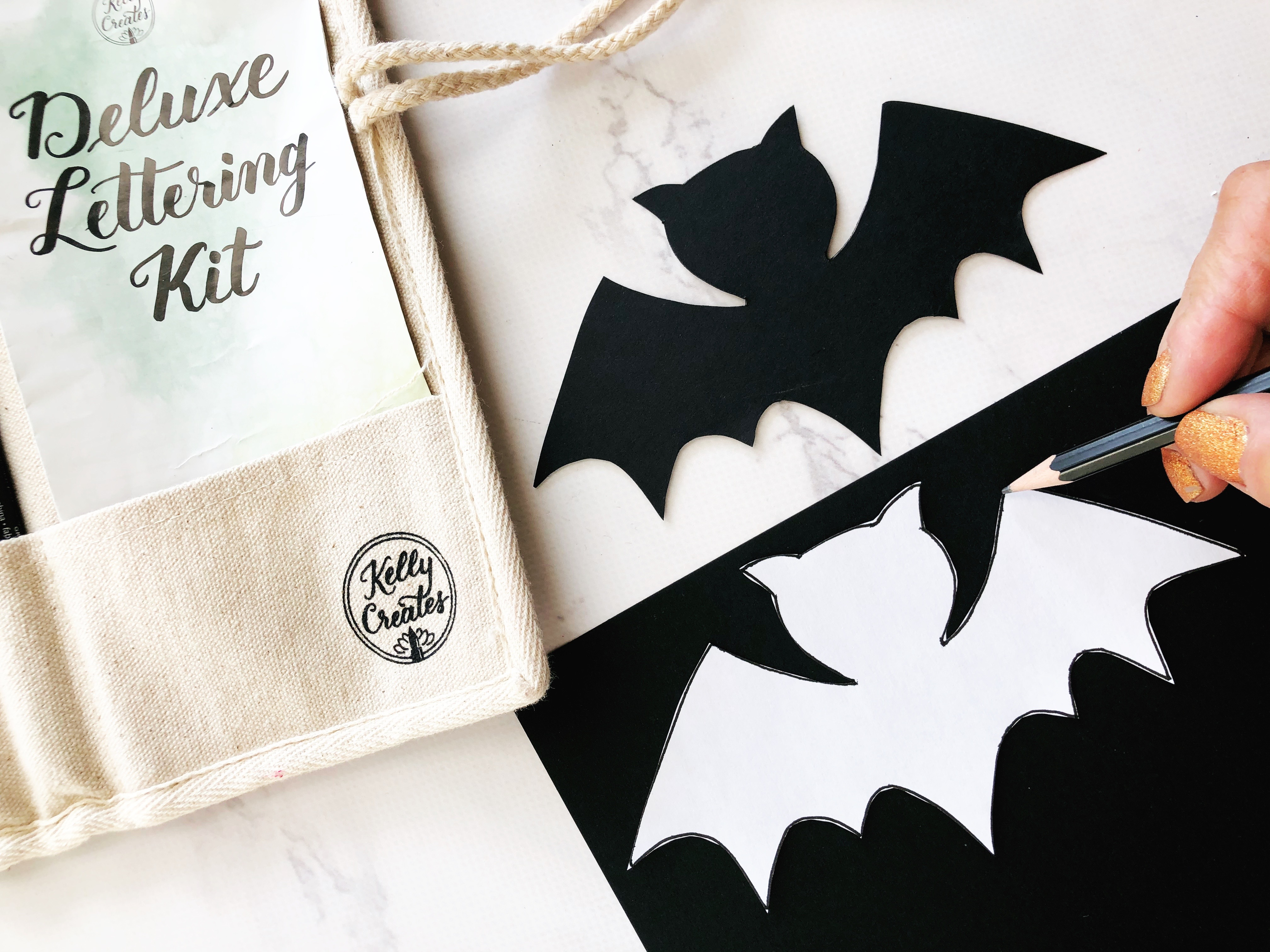 Tracing a bat template onto Kelly Creates black cardstock.