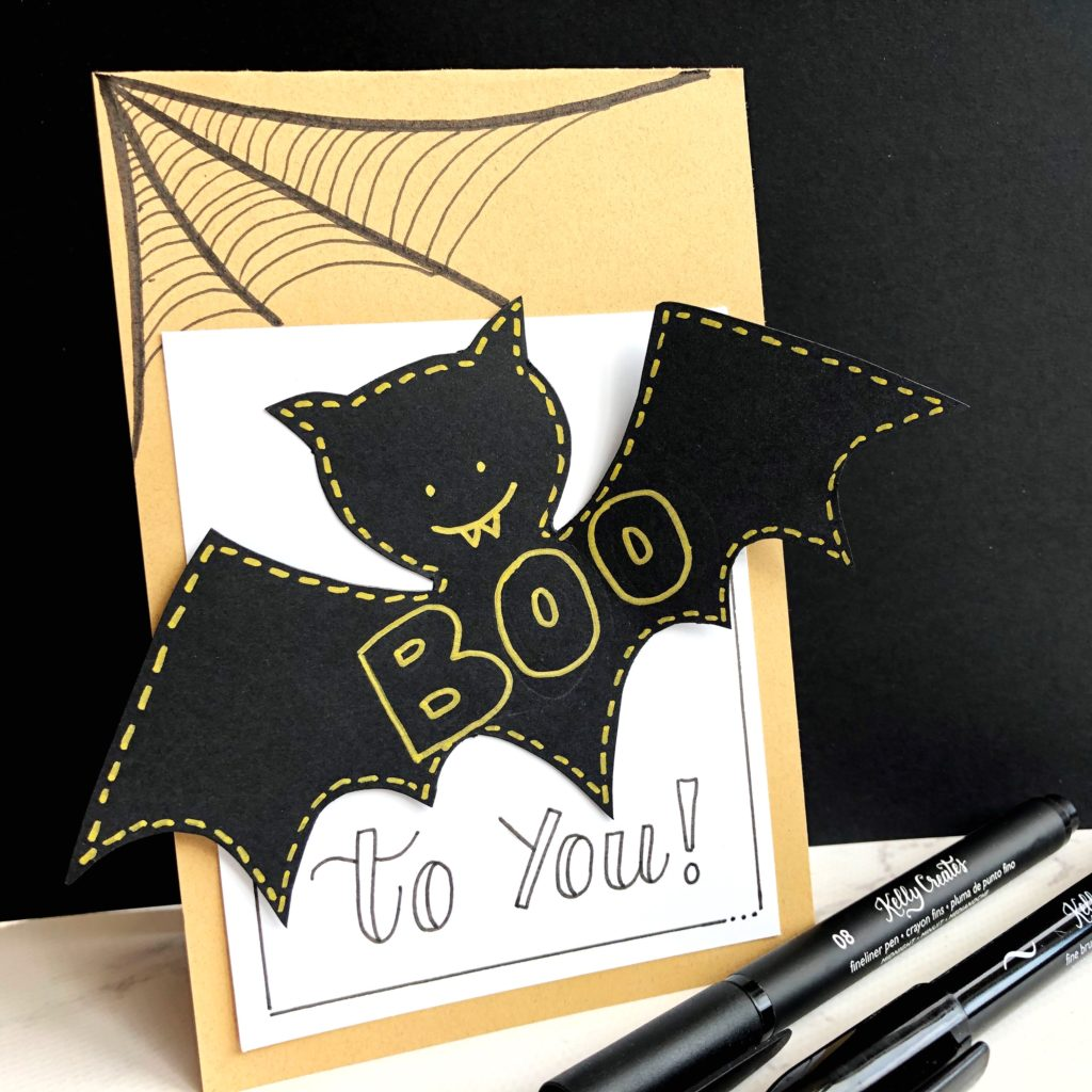 Halloween card designed by Kelly Klapstein with a black bat and spider webs.