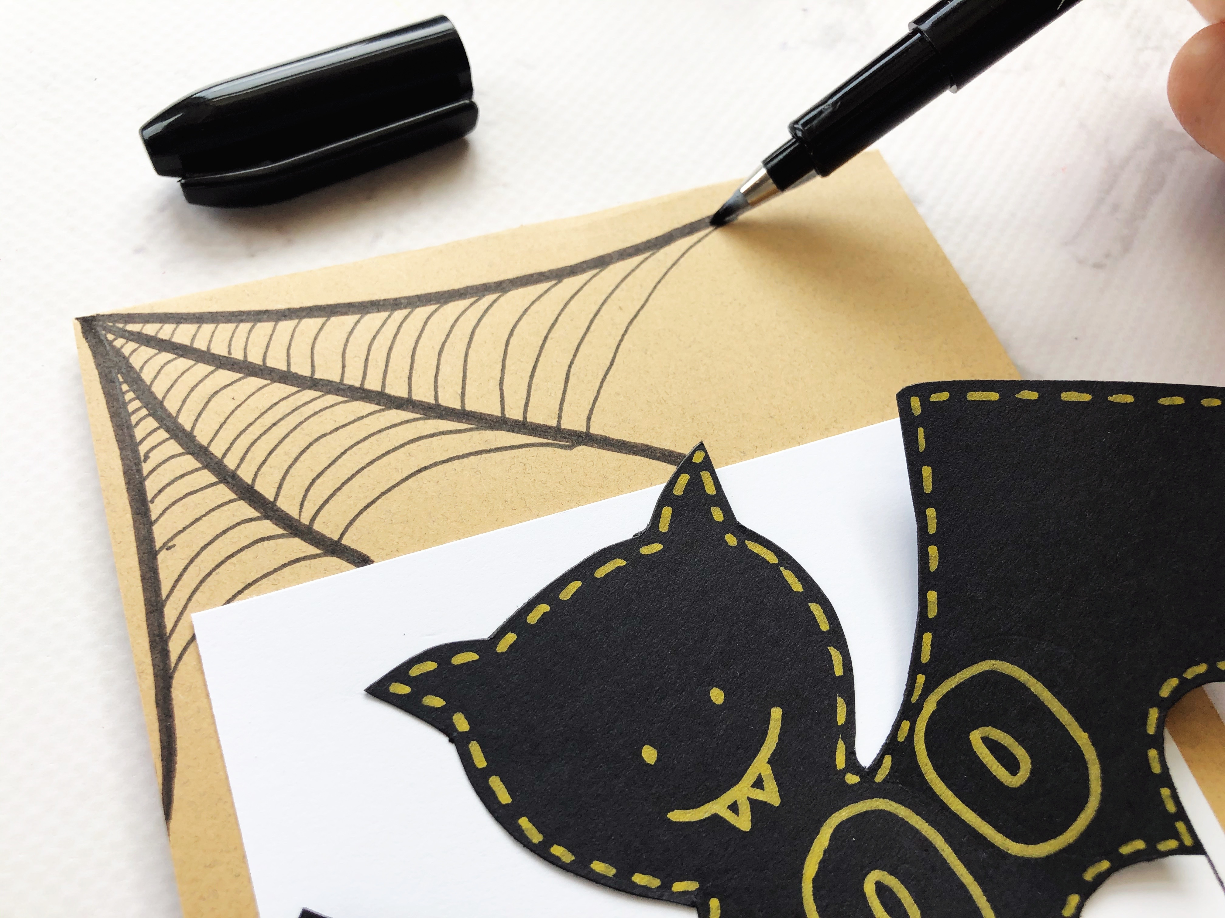 Outlining a hand drawn spider web on a halloween card using a Kelly Creates Black fine liner brush pens.