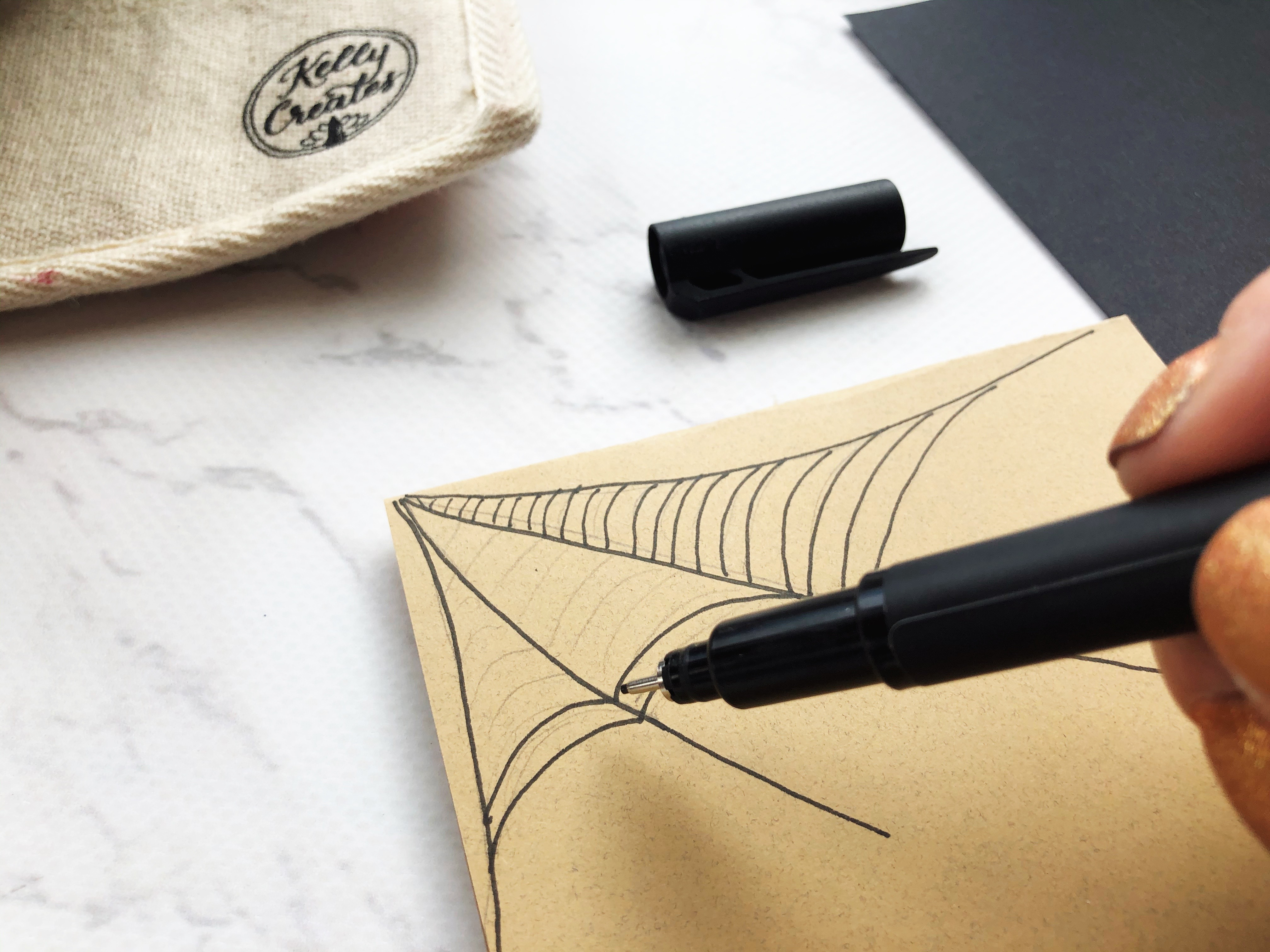 Drawing a spider web on kraft colored cardstock using a Kelly Creates black fineliner pen